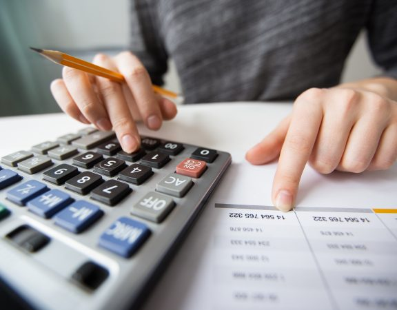 Closeup of accountant counting on calculator and working with table